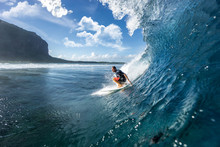 Muscular Surfer Riding On Big Waves On The Indian Ocean Island Of Mauritius