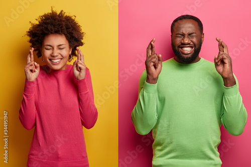 Photo of hopeful lucky Afro America woman and man cross fingers for good luck, b Canvas Print