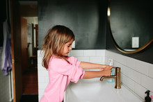 Little Girl Washing Her Hands At The Sink