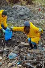 People In Yellow Raincoats Putting Garbage To Blue Bag