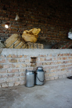 Rural Milk Cans Made Of Steel In Front Of Bricked Wall