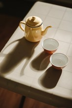High Angle View Of Teapot And Empty Cups On Table