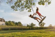 Two Girls Swinging On Tree Swing