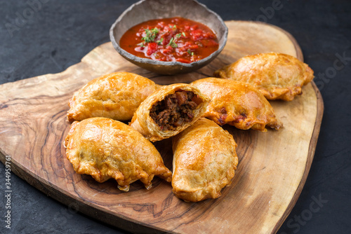 Traditional South American empanada de carne offered with a chili dip as closeup Fototapet