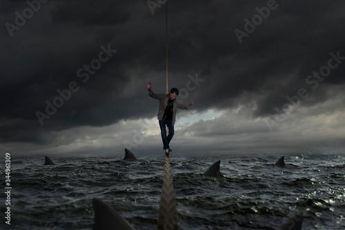 Obraz Tightrope balances on a rough sea full of sharks - fototapety do salonu