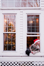 Boy With Santa Hat In Window On Christmas
