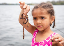 Cute Young Girl With Cornrow Braids Examining The Bait Worms While On The Boat During A Fishing Trip