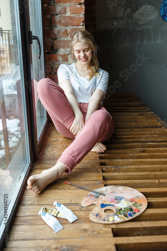 Fototapety, obrazy: stay home, creativity concept: happy female artist on window sill with brush mixing colors on palette. Art, young pretty girl hobby. painting process during COVID-19 pandemic self isolation quarantine