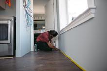 Young Woman Measuring Baseboard