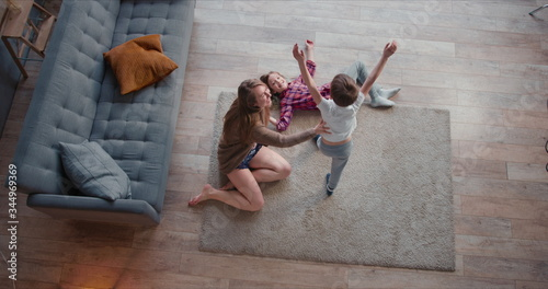 Photo Top view young happy Caucasian mother dancing round with two cute kids, hugging and going crazy on vacation at home