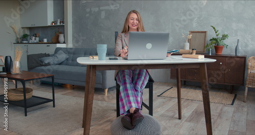Comfortable work from home on lockdown. Young cheerful business woman in pajamas pants using laptop video conference app