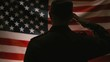 Veterans Day, Memorial Day, Independence Day.The silhouette of soldier enters the frame, salutes and leaves. Back view. The American flag is in the background. Concepts of national American holidays