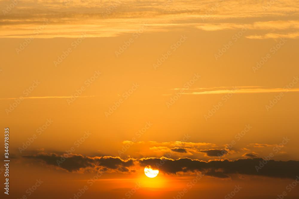 Fototapeta pomarańczowy zachód słońca za chmurami
