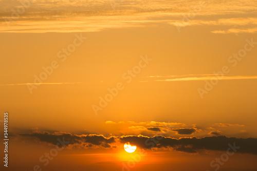 Fototapeta pomarańczowy zachód słońca za chmurami obraz