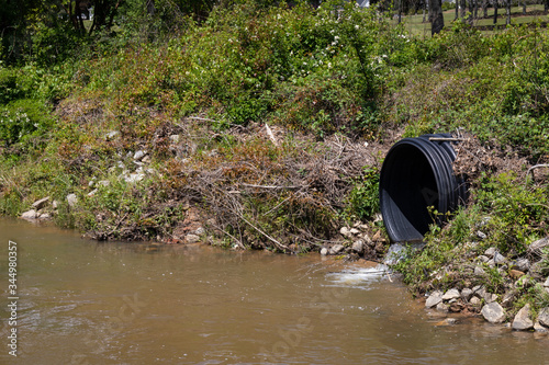 Photo Water entering a stream from a black drainage pipe, runoff environmental polluti