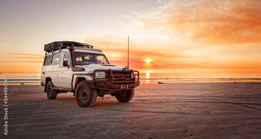 Fototapeta Outback relaxing adventure with 4WD vehicle at the beach of an ocean at sunrise