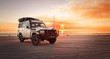 canvas print picture - Outback relaxing adventure with 4WD vehicle at the beach of an ocean at sunrise