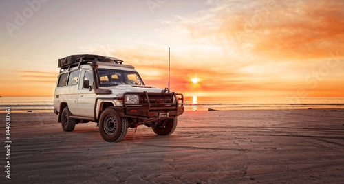Fototapeta Outback relaxing adventure with 4WD vehicle at the beach of an ocean at sunrise  obraz