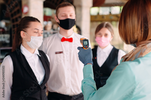 The Manager of a restaurant or hotel checks the body temperature of the staff with a thermal imaging device Fotobehang
