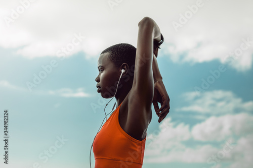 Photo African woman with earphones doing stretching exercise