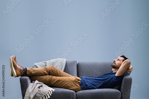 Obraz Man Relaxing On Sofa At Home - fototapety do salonu