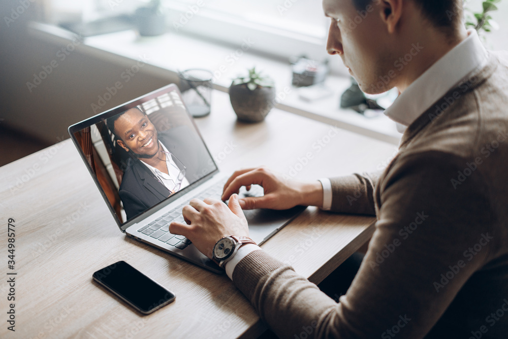 Fototapeta Business partners communicate via video using laptop. The guy talks with his business partner Afro-American appearance about plans and strategy. Distant work