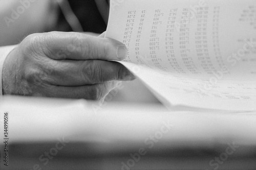 Cropped image of businessman holding spreadsheet at desk in office