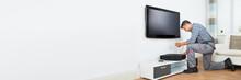 Technician Installing TV Set T...