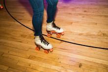 Legs Of People Roller Skating In A Wood Skate Ring.