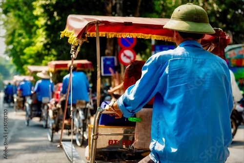 Fényképezés Beautiful shot of a male riding his rickshaw taken from behind