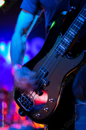 A closeup of a guitarist strumming an electric guitar on stage during a rock music performance at a venue on 6th Street in Austin, Texas Fototapeta