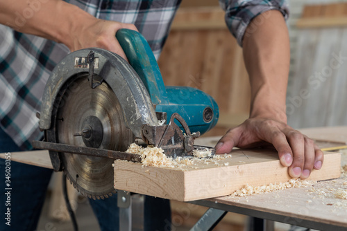 Carpenter working on wood craft at workshop to produce construction material or wooden furniture Canvas Print