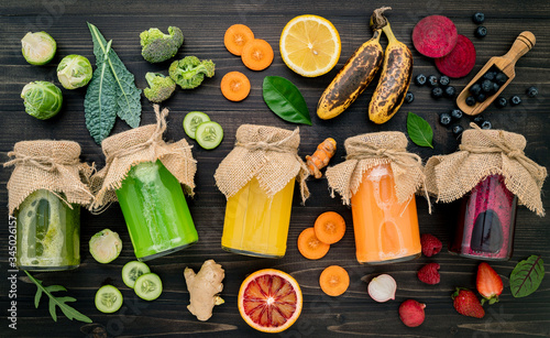 Colourful healthy smoothies and juices in bottles with fresh tropical fruit and superfoods on wooden background..
