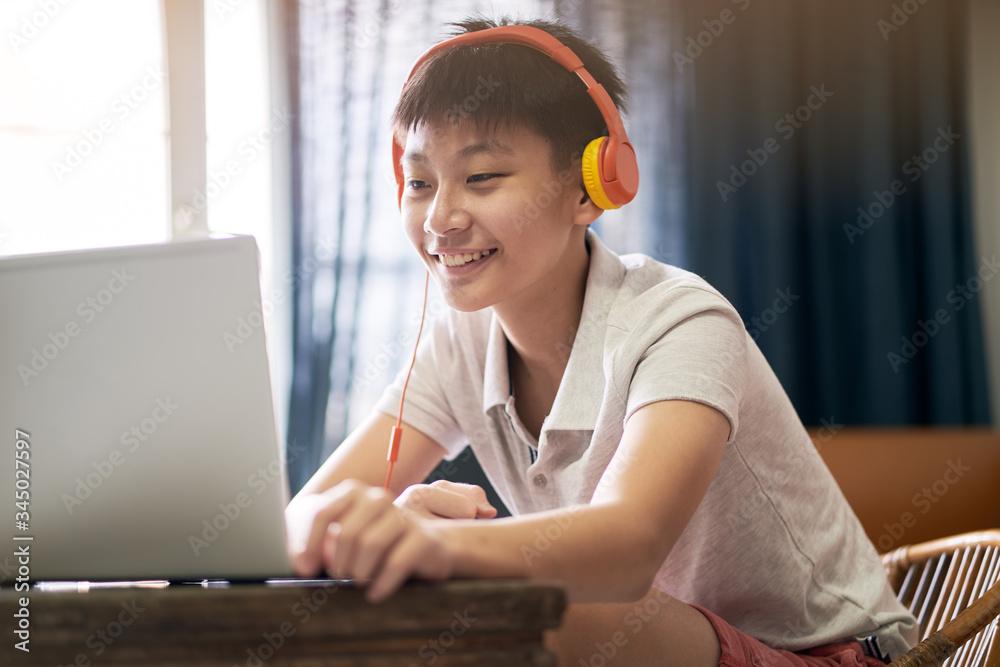 Fototapeta Asian teenage boy studying at home during pandemic wearing headset and smiling
