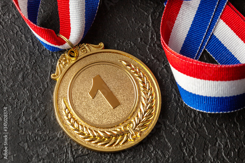 Obraz Gold medal with ribbons. Award for first place in the competition. Prize to the champion. Black background - fototapety do salonu