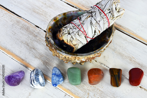 A close up image of healing chakra crystals with a white sage bundle in an abalone shell Wallpaper Mural