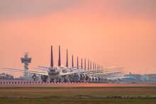 Aircraft Parking At Airport Runway At Sunset Cause By COVID-19 Pandemic Outbreak Make Airline Stop Operation.