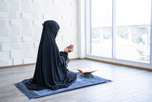 Portrait Of Beautiful Asian Muslim Woman With Her Palm Open Praying To Allah Wearing Black Hijab Robe Covering The Head, Praying In A Prayers Room With Quran And Bead Sitting On Knees On Vintage Rug