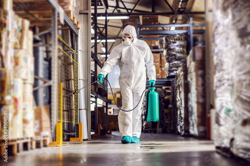 Obraz Man in protective suit and mask disinfecting warehouse full of food products from corona virus / covid-19. - fototapety do salonu