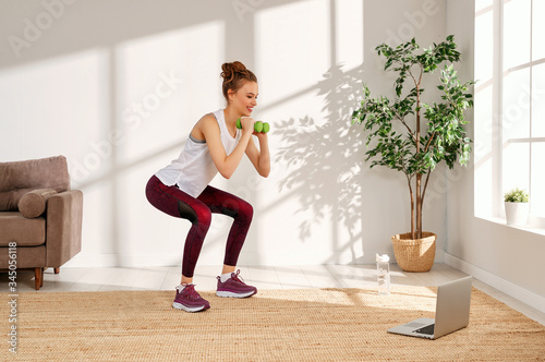 Young woman squatting with dumbbells at home. Fototapete
