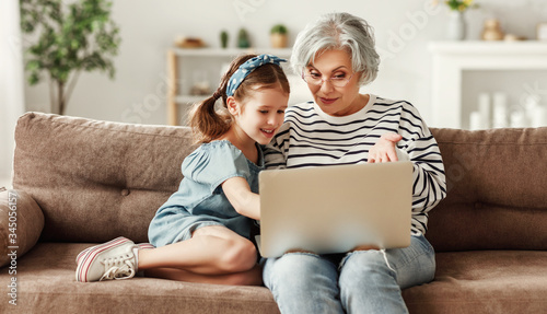 Fototapeta Happy aged woman with cute granddaughter smiling  while sitting on sofa and using laptop in living room. obraz