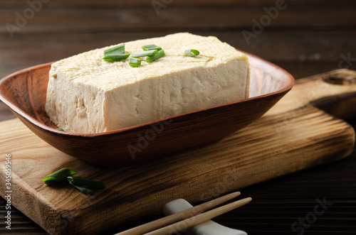 Fotomural Soybean tofu vegetable bean curd in clay bowl on kitchen table with chives and c