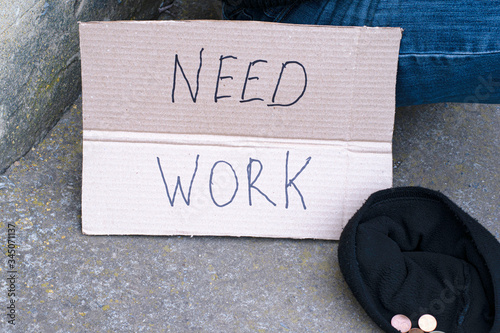unemployed man sitting on the ground holding the cardboard sign saying need work Canvas Print
