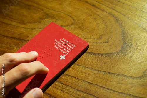 Single Swiss passport on a wooden table Canvas-taulu