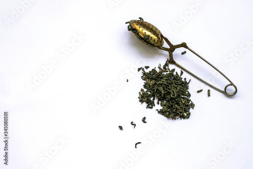 Valokuvatapetti Green tea in a teaspoon on a white background