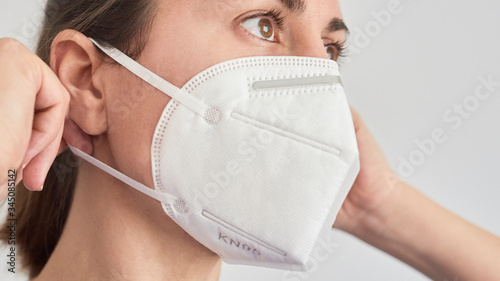 Close up picture of a brunette woman wearing a KN95 FPP2 mask. Fototapet