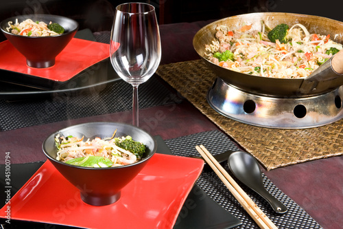Asian stir fry dish with chop sticks and black and red plates Wallpaper Mural