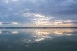 Breathtaking scenery of the sunset sky with storm clouds reflecting on the water surface