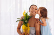 Caucasian little girl in blue dress is kissing her mom and giving her yellow flowers