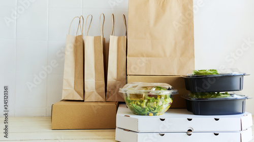 Fototapeta Different paper packages and containers for takeaway food on table. Takeout meal, deivery to home, food delivery, online shopping concept. obraz